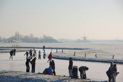 Frozen Canals in Holland. Dutch Winter Landscape. Ice skaters in a Dutch Winter in a landscape with windmills Stock Image