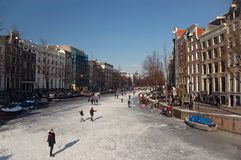 Frozen Canals. Wide angle view of pedestrians and skaters in the winter sun on a frozen canal in Amsterdam Royalty Free Stock Images