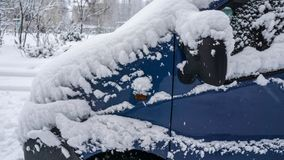 Frozen car, blue minivan covered snow at winter day. Urban scene of city life in winter stock image