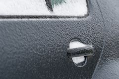 Frozen car door covered in ice on a winter morning Stock Photo