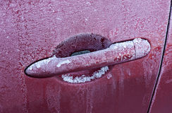 Frozen car handle. Handle of red car covered with frost at winter Royalty Free Stock Image