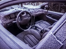 Frozen car. Photograph of a old broken car let in a field covered with ice Stock Photo