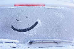 Frozen car window. Drawing on the rear window of a car made by hand Stock Photography