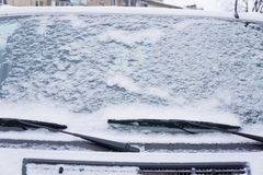 Frozen car windshield covered with ice and snow on a winter day. Close-up stock images