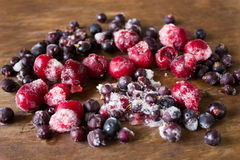 Frozen cherries and black currant on ice stock images