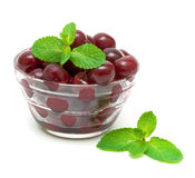 Frozen cherries and mint sprigs on a white background Stock Photography
