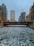 A frozen Chicago River with cracked ice chunks during frigid January evening. Commute in winter royalty free stock image