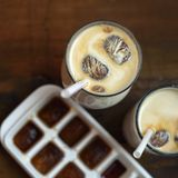 Frozen coffee cubes with milk - cocktails on dark wooden table. Top view Stock Photo
