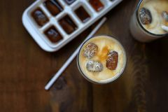 Frozen coffee cubes with milk - cocktails on dark wooden table. Top view Stock Photos