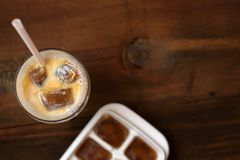 Frozen coffee cubes with milk - cocktails on dark wooden table. Top view Royalty Free Stock Photo