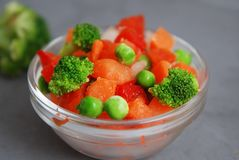 Frozen Colorful Vegan Healthy Vegetables. Brocolli, Carrots, Peas, Pepper. vertical Image. Gray Background. stock photos