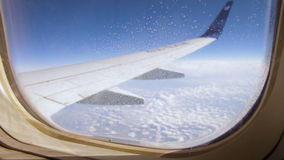 Frozen condensation of ice crystals on the window of an airplane. With the wing in the back stock video footage