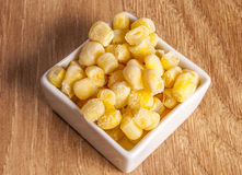 Frozen corn. White bowl of uncooked frozen corn, on wooden background Stock Image