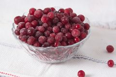 Frozen cranberry berries in a plate on a white tablecloth.  Stock Photo