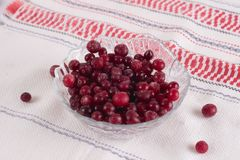 Frozen cranberry berries in a plate on a white tablecloth.  Royalty Free Stock Photography