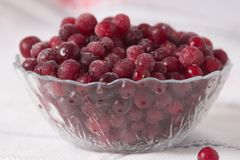 Frozen cranberry berries in a plate on a white tablecloth.  Royalty Free Stock Photo