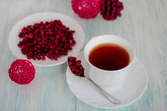 Frozen cranberry, cup of tea on wooden background Stock Images