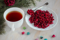 Frozen cranberry, cup of tea on wooden background. Frozen cranberry and cup of tea on wooden background top view with plate, spoon, christmas tree and Royalty Free Stock Image