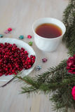 Frozen cranberry, cup of tea on wooden background. Frozen cranberry and cup of tea on wooden background top view with plate, spoon, christmas tree and Stock Photography