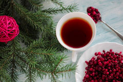 Frozen cranberry, cup of tea on wooden background. Frozen cranberry and cup of tea on wooden background top view with plate, spoon and christmas tree health Stock Photography