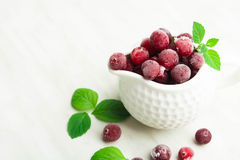 Frozen cranberry in white sauce pan with fresh mint. Over light table with copy space Royalty Free Stock Photography