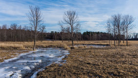 Frozen creek winding through farm fields Royalty Free Stock Images