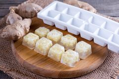 Frozen cubes of ginger. On the table Stock Photos