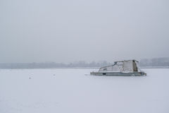 Frozen Danube river with captured boats and seagulls Stock Image