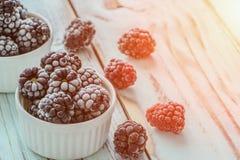 Frozen Dewberries in hoarfrost on rustic wooden table5. Close up. Frozen Dewberries in hoarfrost on rustic wooden table. Selective focus. Toned. Close up Stock Photos