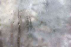Frozen drops on frosted glass. Winter textured background. Stock Photo