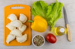 Frozen dumplings on cutting board, condiment, oil, vegetables an Royalty Free Stock Images