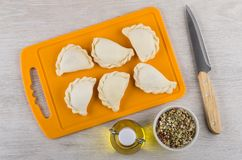 Frozen dumplings on cutting board, condiment, vegetable oil and Royalty Free Stock Photography