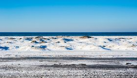 Frozen dunes on beach against water and sky. Frozen ice and sand dunes on beach in winter by empty lake horizon under clear blue sky, near Georgian Bay, Ontario Stock Image