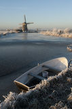 Frozen dutch river. A Dutch landscape of a frozen river with an rowboat and old windmill Stock Photos