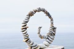Frozen Equilibrium. White spiral of pebbles on the boulder at the sea stock photography