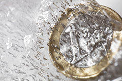 Frozen Euro coin melting Stock Images
