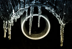 Frozen Exhuast. A detailed close up of the exhaust pipe of a car covered in ice and icicles royalty free stock photos