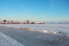 Frozen farm. A sunny winter day in Dutch landscape Royalty Free Stock Image