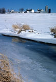 Frozen Farm1. A stream is iced over with a farm in the background Royalty Free Stock Photos