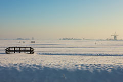 Frozen farmland with windmill in background. A sunny winter day in Dutch landscape Royalty Free Stock Photos