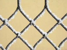 Frozen fence. Part of decorative lattice covered with snow, close-up Stock Images
