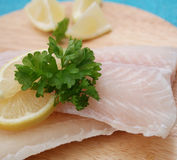 Frozen fish. Some frozen fish with lemon on a wooden plate Royalty Free Stock Images