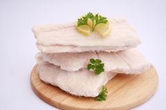 Frozen fish. Some frozen fish with lemon on a wooden plate Royalty Free Stock Photos