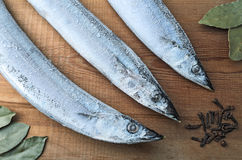 Frozen fish Pacific Saury on a wooden board with spices. Frozen Pacific Saury on a wooden cutting board with spices (a bay leaf and cloves). Healthy eating. Fish Stock Image