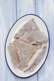 Frozen fish in white dish in blue background Stock Photo