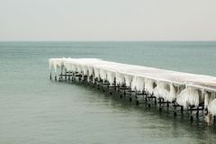 Frozen fishing pier with hanging icicles Royalty Free Stock Photo