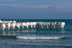 Frozen fishing pier with hanging icicles in a sunny winter day Royalty Free Stock Photo