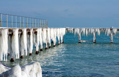 Frozen fishing pier with hanging icicles in a sunny winter day Stock Image