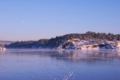 Frozen fjord in the evening with moon Stock Photos