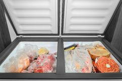 Frozen food in the freezer. Bagged frozen meat and other foods in a horizontal freezer with the two doors open. Food preservation Stock Image